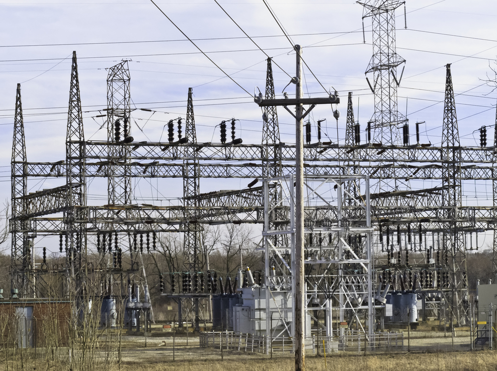 Electrical substation with towers and various steel lattice structures, with telephone pole in foreground, before sunset in spring